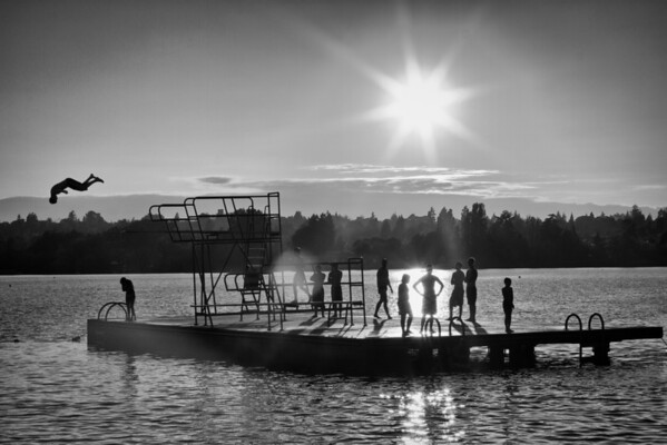 As the sun sets on Green Lake, kids enjoy diving from a floating platform.