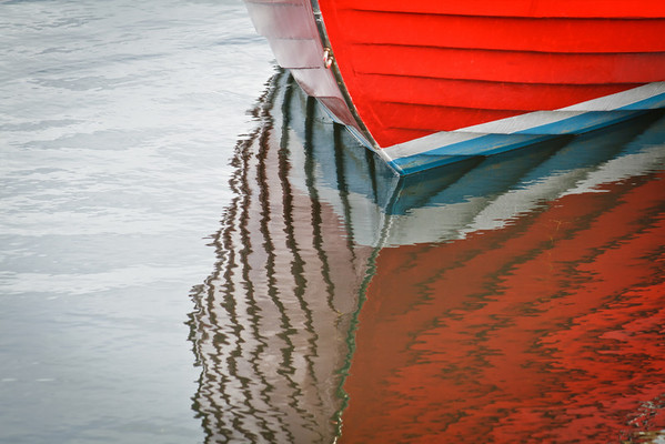 A wooden boat's reflection moored in Ballard.